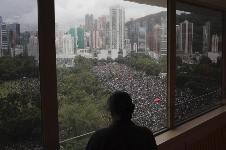 Osoba sa pozerá z okna na protest v parku Victoria v Hongkongu. Zdroj foto: TASR/AP Photo/Kin Cheung)
